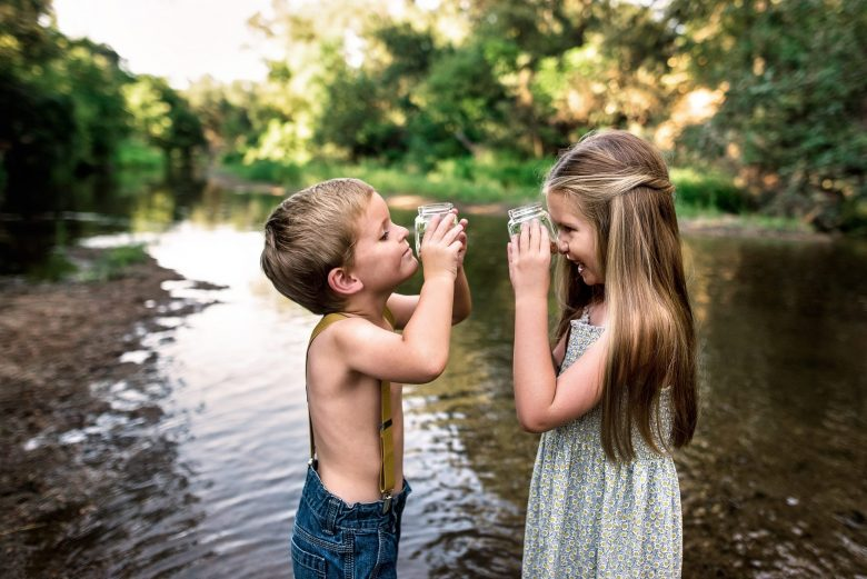 playing and getting wet in the creek during a childs photo session in gig harbor