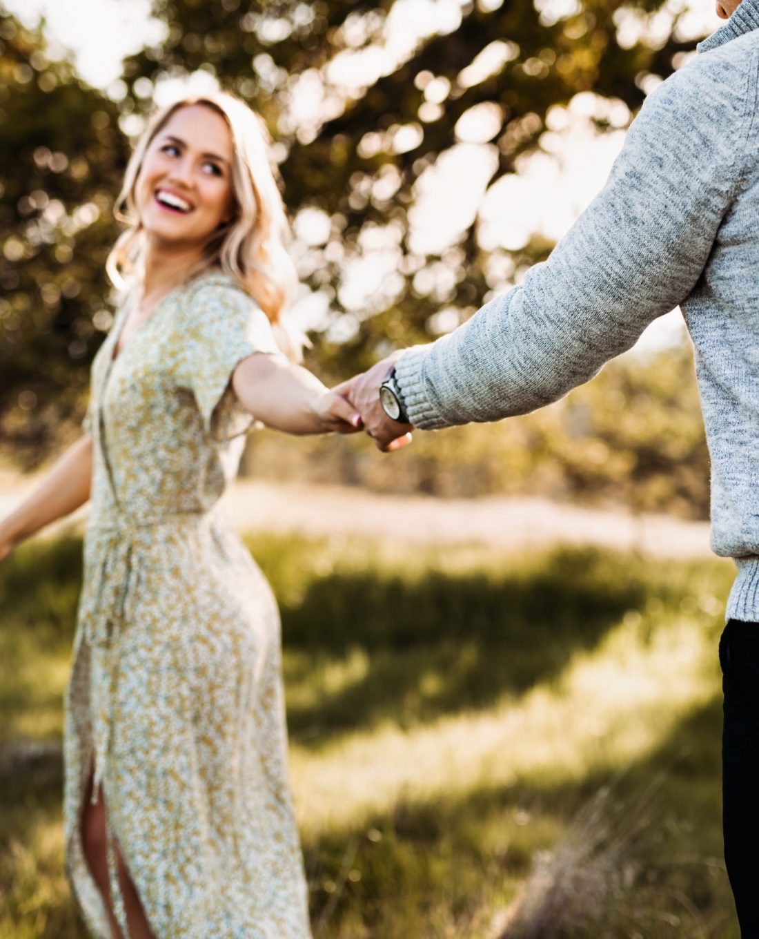 blond lady in a green dress pulls her fiance across a grassy field