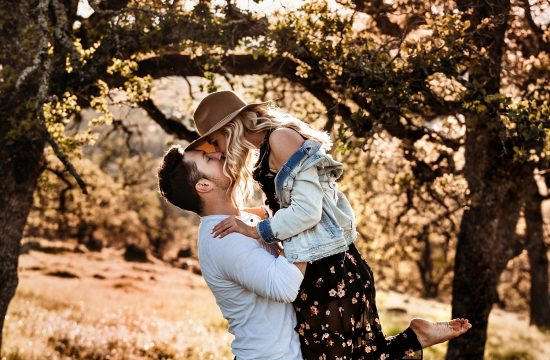 adventure travel sessions, engaged couple kissing at sunset in the hills