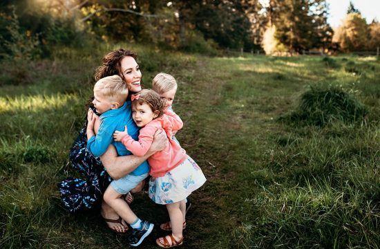mama hugs her three babies in a grassy field in Port Orchard, mommy and me photo session, family session port orchard,