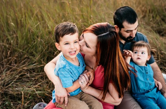 mommy kissing son as they sit with family in a grassy field, maternity photo session, photo session lifestyle